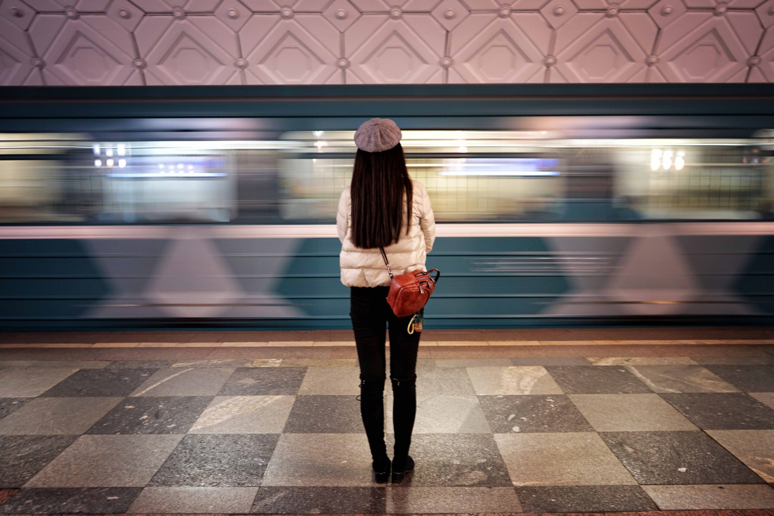 train whizzing by a woman at the station